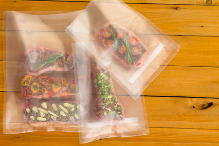 Multiple random meat dishes with bits of vegetables inside plastic bags sitting on wooden plank table