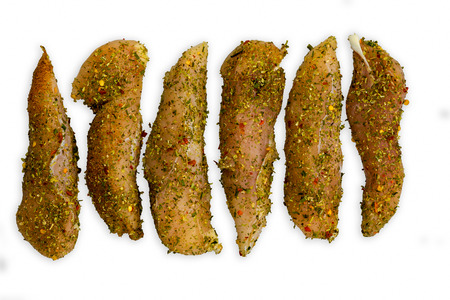 Long pieces of unknown meat covered in seasoning sitting on top of completely plain white background
