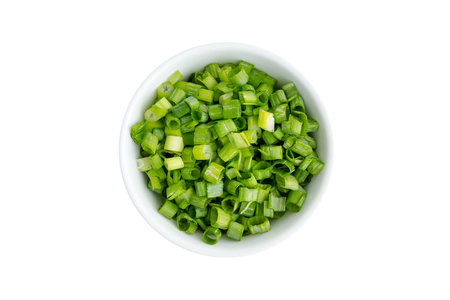 Finely chopped fresh green onions in a generic ceramic ramekin viewed from above isolated on white