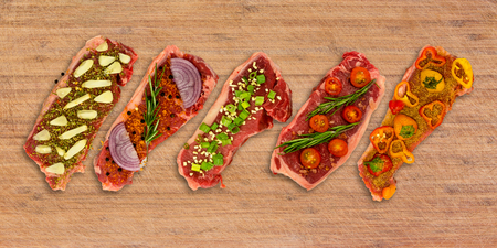 Conceptual clean view of five vegetable seasoned New York Strips on cutting board