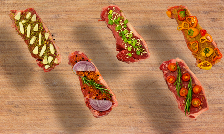 Conceptual floating view of five New York Strips on cutting board seasoned with colorful vegetables Фото со стока