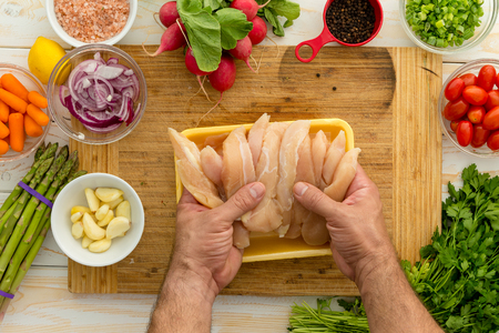 Chef preparing chicken strips with vegetables and seasonings on cutting board for dinner perhaps lunch Фото со стока