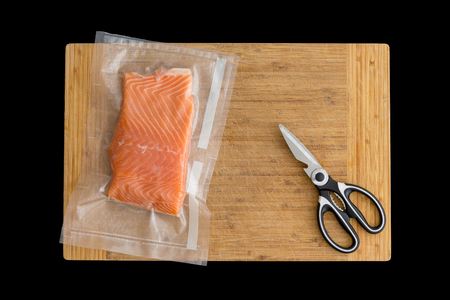 Fillet of fresh Atlantic salmon packaged fro freezing in a vacuum pack of clear plastic lying on a wooden board with scissors