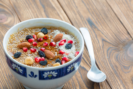 Small asure bowl of tasty cereal with nuts and fruit next to small spoon sitting on brown wood plank table