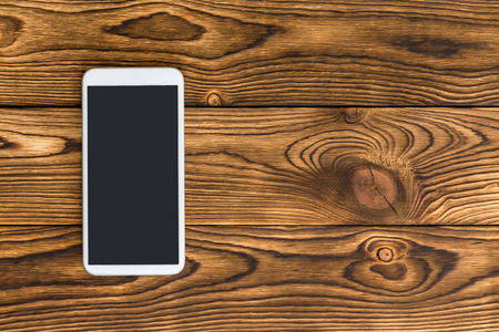 Smartphone lying against wooden background Фото со стока