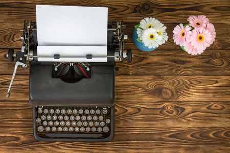 Overhead view of vintage metal typewriter next to blue and pink flowers sitting on wooden plank table Фото со стока