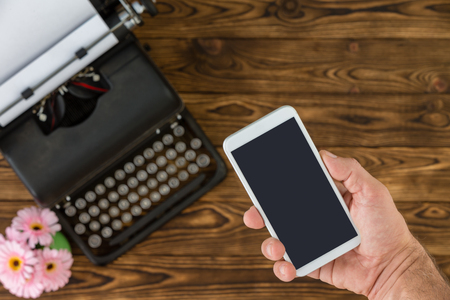 White smart phone next to black metal vintage typewriter and small pink flowers