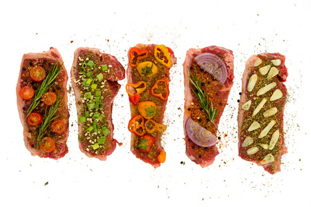 Five New York Strips deliciously seasoned in different ways with colorful vegetables isolated on white