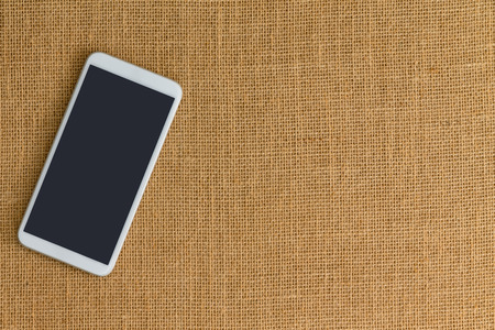 One white smart phone sitting on surface made up of light brown crisscrossed thread. Фото со стока