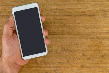 Overhead view of unidentified man using hand to holding smart phone over scratched wooden background