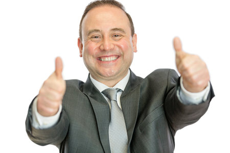 A happy, excited, mature businessman giving thumbs up signals with both hands on a white  with copy space.