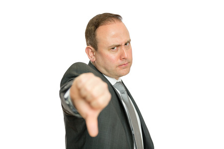 A portrait of a stern, angry business man giving a thumbs down signal on a white  with copy space.