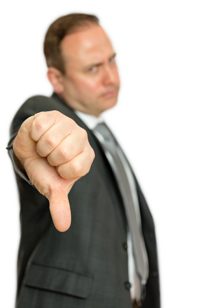 A portrait of an annoyed, angry business man giving a thumbs down signal on a white  with copy space.