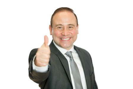 A happy, smiling businessman giving a thumbs up signal with a white  and copy space.