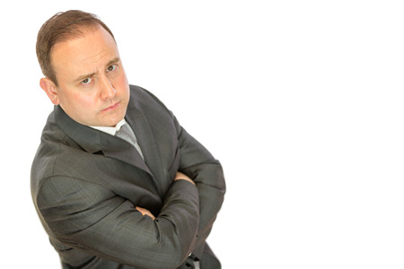 A serious-looking, concerned business manager with folded arms on a white  with copy space.