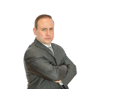 An angry, stern businessman with crossed arms on a white  with copy space.