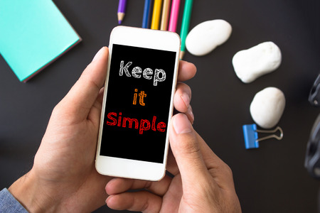 cogent: Keep it simple, text message on screen at hands take smartphone, black table with office supplies backdrop background . business concept.