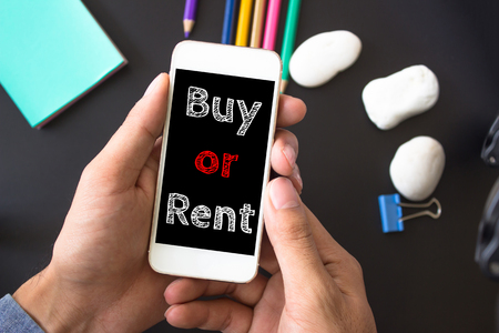 first time buyer: Buy or rent, text message on screen at hands take smartphone, black table with office supplies backdrop background . business concept.