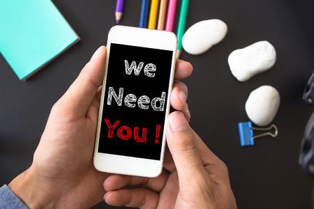 Abbiamo bisogno di te, il messaggio di testo sullo schermo a mano prende smartphone, tavolo nero con forniture per ufficio, sfondo. concetto di business.