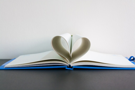 Pages of a book curved into a heart shape on table