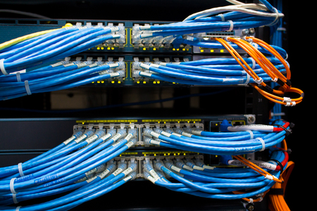 rack arrangement: front side of working data servers with flashing LED lights Stock Photo