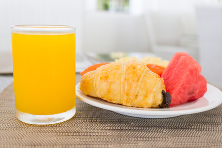 fruit plate: Breakfast with orange juice, croissant and fruits on dinning table