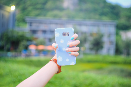 Daisy flower phone case and the hands with blue nails.