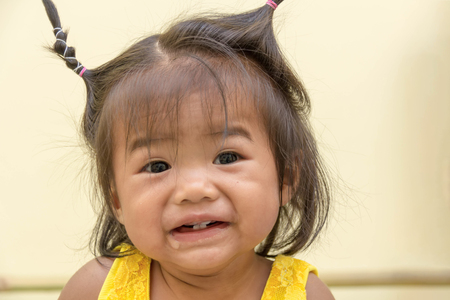 A ten-month-old girl wearing a yellow coat, Happy smile with just four teeth that she has and drooling.