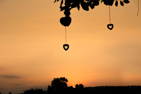 Evening sun with a silhouette heart hanging on a tree.