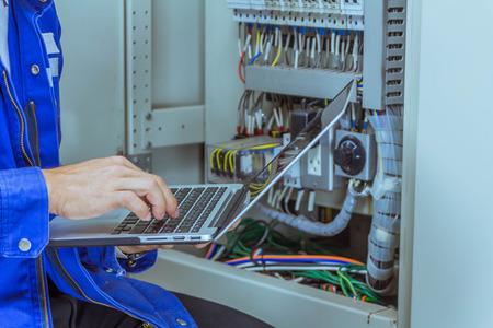 Los ingenieros masculinos están comprobando el sistema eléctrico por programa en la computadora portátil.