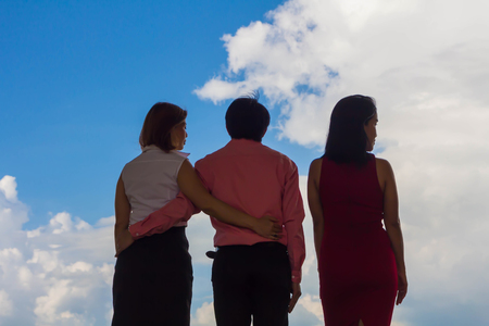 Man and woman embrace each other and one woman is standing with jealousy. Stock Photo