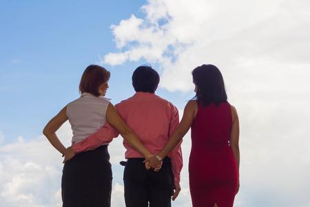 L'uomo e la donna si sono abbracciati, ma la donna a cui ha stretto segretamente la mano perché si ama. Archivio Fotografico