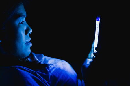 Women she played the smart phone in the dark light and the blue light has a negative effect on the eyes.