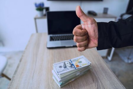 Mans hand showing thumb up - like sign with many money on background, Businessmen who work actively and financially successful. Stockfoto