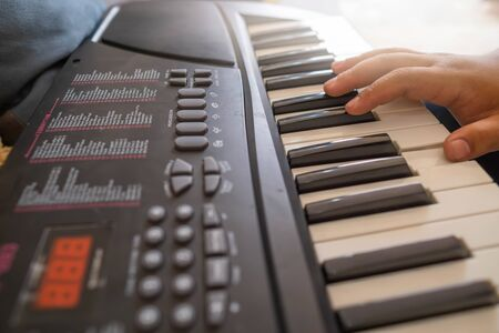 Hands of the child are playing the keyboard or piano for music lessons, music concept.