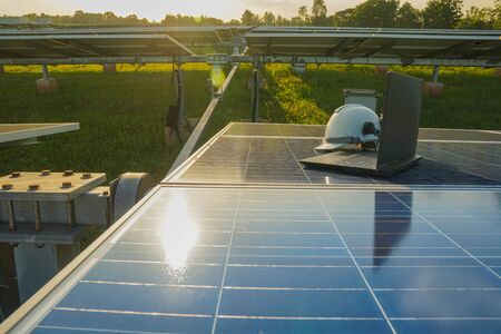 The white safety helmet and labtop of the engineer who examined the operation of the electrical system, placed on a blue solar cell, Photovoltaic module idea for clean energy production. Standard-Bild