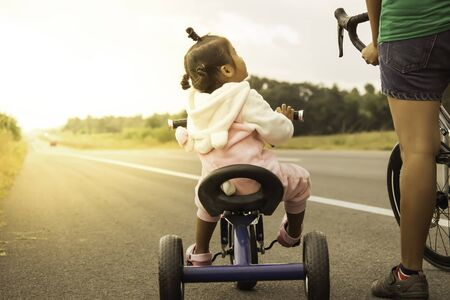 A picture of the warmth of a mother who is teaching her child to ride a bicycle, which the mother will take care to not be dangerous, public road in the evening with the orange light of the sunset.