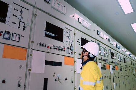 Male engineer wearing a yellow uniform and wearing a white safety hat, inspecting electrical systems in a large power plant.