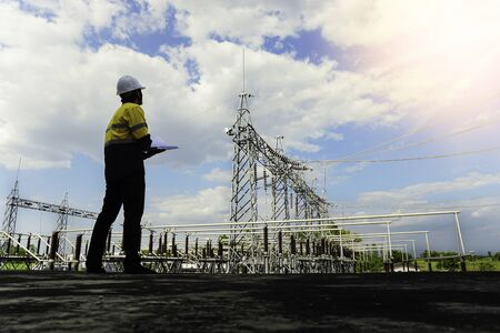 A low-angle view of the engineer looking at the drawing of a small size power plant to verify installation accuracy to meet standards. The background is the structure of the power plant with blue sky. Stock Photo