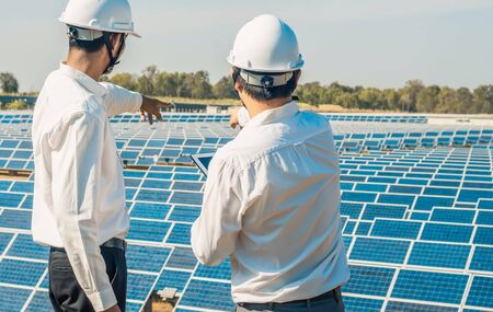 La ferme solaire (panneau solaire) avec deux ingénieurs parle de la capacité de production, de l'énergie alternative pour conserver l'énergie mondiale, de l'idée de module photovoltaïque pour la production d'énergie propre.