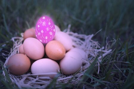 There are many eggs that are stacked together and have pink eggs is decorated with colorful colors are floral patterns put on top of the green grass background. Happy Easter day concept. Фото со стока