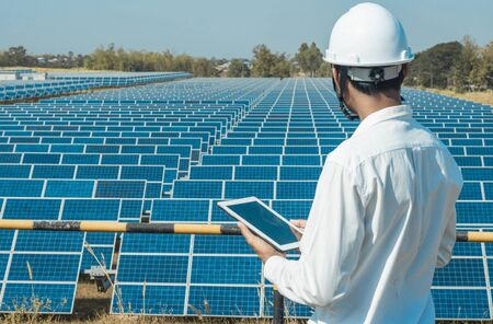 The solar farm(solar panel) with engineers walk to check the operation of the system by laptop, Alternative energy to conserve the world's energy, Photovoltaic module idea for clean energy production. 版權商用圖片