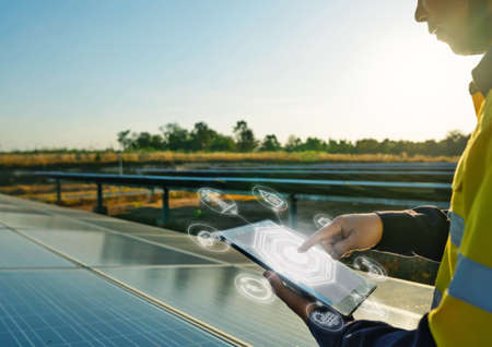 The solar farm(solar panel) with engineers is checking the operation of the system by laptop, Alternative energy to conserve the world's energy, Photovoltaic module idea for clean energy production.