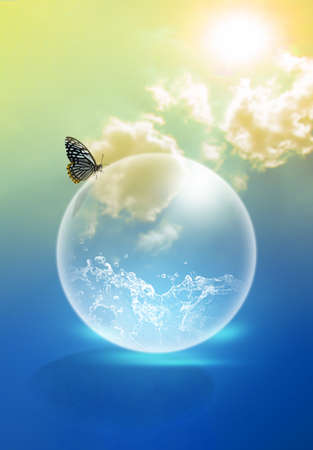 The water in a soap bubble is a concept of water conservation, with butterflies on top of it and a backdrop of the sky and the orange sun to represent a hot climate. Saving water idea.