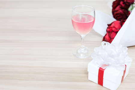 Wine glass put on the wooden table with a gift and red rose, Concept of happiness in giving and receiving gifts from someone special.