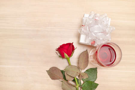 Gift and red rose to put on the wooden table with a wine glass, Concept of happiness in giving and receiving gifts from someone special. Imagens