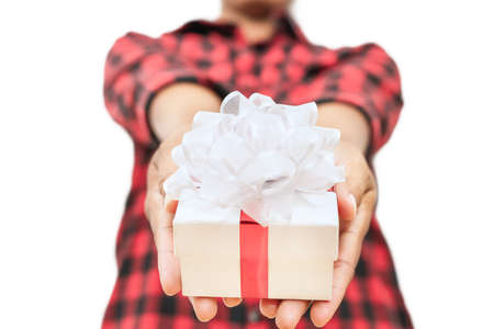A gift box in the hand of a woman wearing a red-black scotch shirt on white background, Isolated. Concept of Happiness in receiving gifts from someone special. 免版税图像