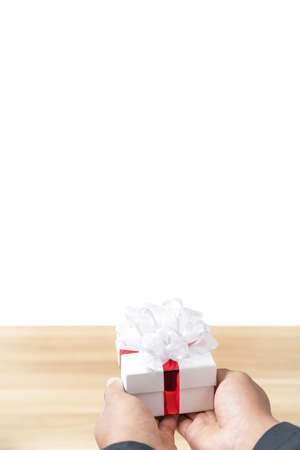 A gift box in the hand of a man wearing a black suit on white background, Concept of happiness in giving gifts to someone special. Isolated.