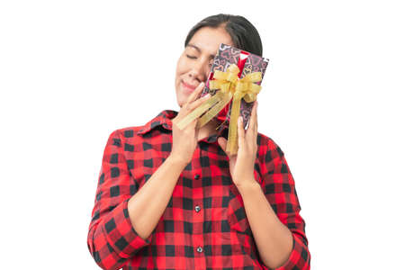 A gift box in the hand of a woman wearing a red-black scotch shirt on white background, Isolated. Concept of Happiness in receiving gifts from someone special. Imagens