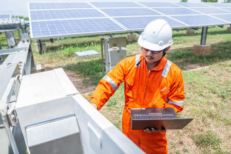 Engineers used a laptop for checking the performance of the controller box to confirming systems working normally. Concepts professional engineer for the Solar cell power plant. Imagens